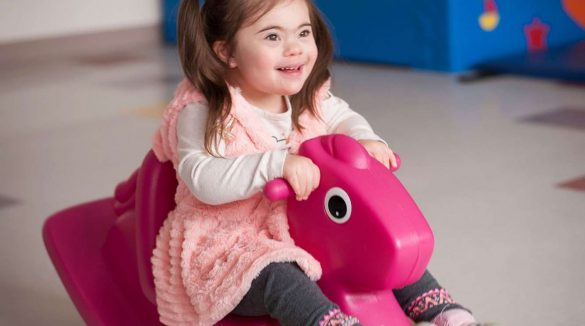 Little girl riding a rocking horse and smiling from enjoyment