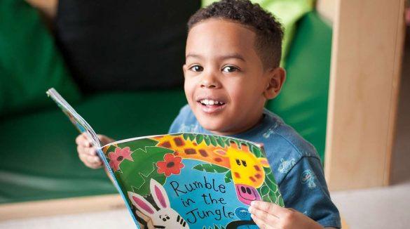 Little child smiling at camera with a book in his hand
