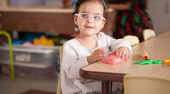 Little girl with glasses seated playing with toys on table