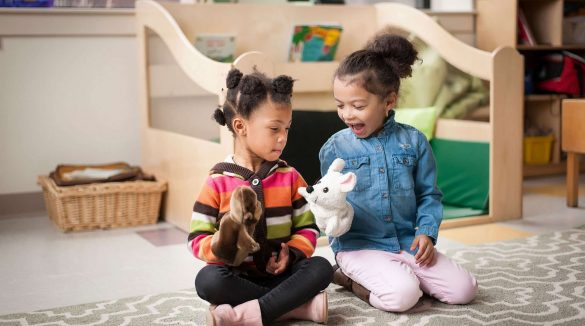 Two littler girls playing with a doll in a playroom