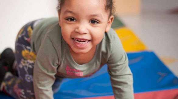 Little child crawling while smiling at the camera