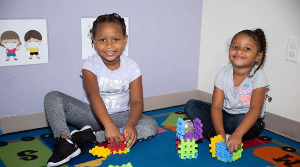Two girls building puzzle cubes while smiling at the camera