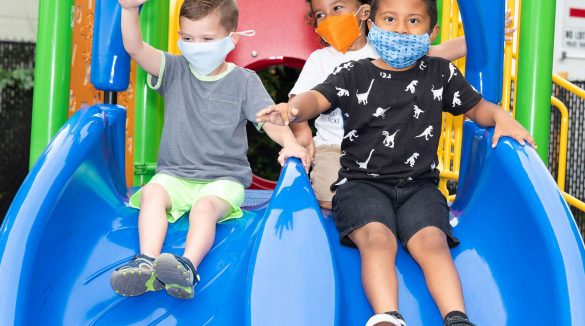 Group of children wearing face masks going down slide