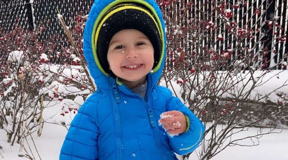 Litte boy in blue snowsuit smiling at camera while outside in the snow