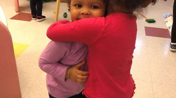 Two little girls hugging inside a classroom